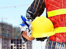 trabalhador segurando capacete amarelo e luvas, e uma obra ao fundo
