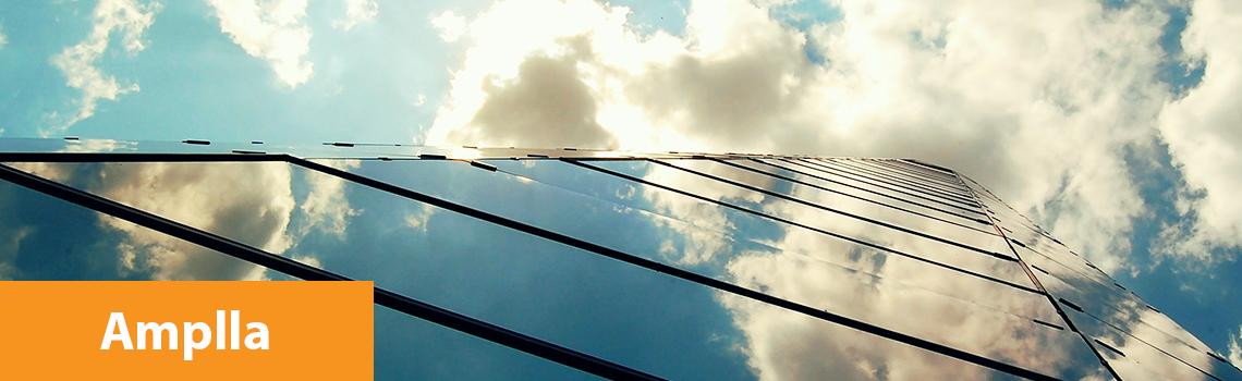 foto de um prédio com fachada de vidro, de baixo para cima, mostrando o céu