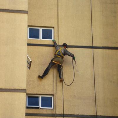 trabalhador realizando a lavagem mecanizada das paredes de um prédio