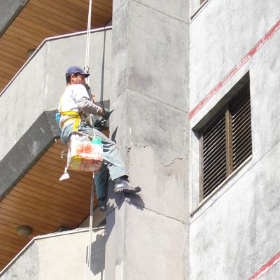 trabalhador realizando a remoção de quartzo das paredes de um prédio